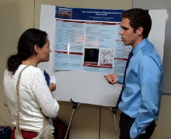 Caleb Schmid, MD Resident describes his research to fellow Resident Emily Zarookian, MD