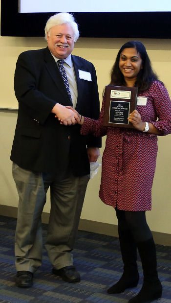 Governor Warren Evins presents the Chapter Service Award plaque to Dr. Aditi Singh.