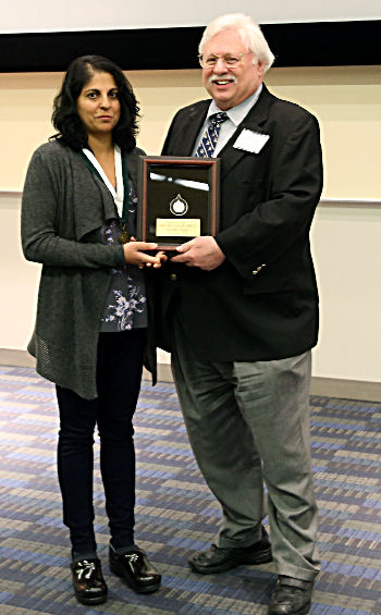 Governor Warren Evins bestows the Chapter Laureate Award, plaque, and medallion to Dr. Sandhya Wahi-Gururaj.